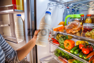 Woman takes the milk from the open refrigerator