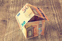 Money house on wooden background