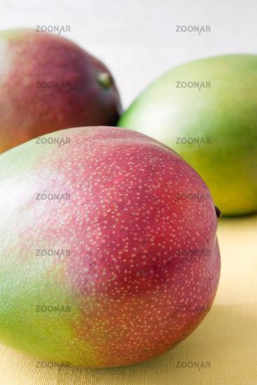 Nahaufnahme mit geringer Tiefenschärfe von drei Mango Früchten auf einer gelben Tischdecke.