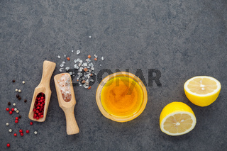 The lemon vinaigrette dressing ingredients lemon, olive oil, himalayan salt and pepper corn on dark stone background with flat lay and copy space.