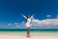 Woman with raised arms on beach