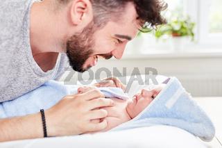 Vater und Baby in Handtuch gewickelt