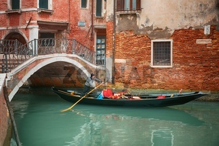 Gondolier on his gondola under the bridge, sail through the canal in Venice, Italy