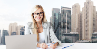 businesswoman with notepad and laptop at office