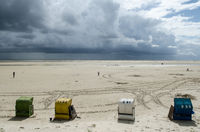beach with beach chairs an stormy clouds