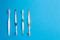 Multi-colored toothbrushes on blue background