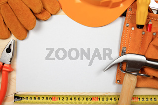 Construction helmet and tools on wooden background