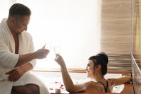 Young couple drinking champagne in sauna