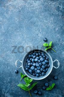 Fresh Blueberries in a bowl on dark background, top view. Juicy wild forest berries, bilberries. Healthy eating or nutrition.