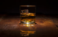 Glass of whiskey with ice cubes served on wooden planks.