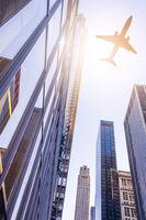 plane over modern buildings