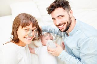 Glückliches Eltern Paar gibt Baby die Flasche