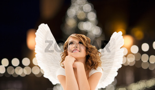 happy woman with angel wings over christmas lights