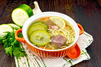 Soup with zucchini and noodles in bowl on kitchen towel