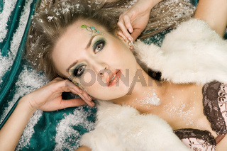 woman lying on green silk with snow