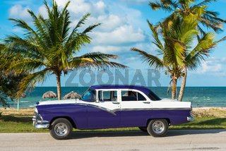 Amerikanischer blau weisser Oldtimer parkt am Strand unter Palmen in Havanna Cuba
