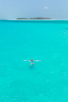 Woman snorkeling in clear shallow sea of tropical lagoon with turquoise blue water.