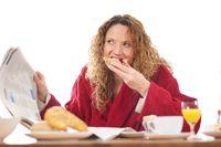 woman reading newspaper and having breakfast