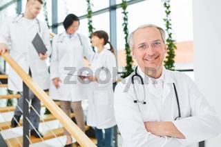 Oberarzt steht selbstbewusst vor seinem Team