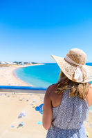 Woman wearing a hat, standing at viewpoint over, Albufeira beach on the Algarve, Portugal