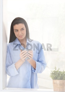 Woman looking out of window with coffee