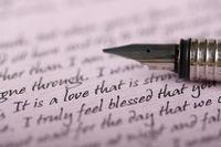 A pen on a love letter written on purple paper
