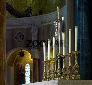 Ornate candlesticks on altar in church with gold cross