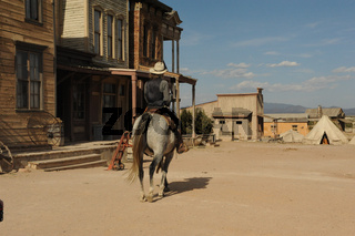 Cowboy rides his horse down a old-fashioned western town in a western city.