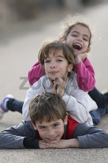 Three children lying on the floor one on top of the other.