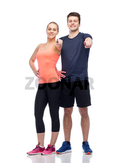 happy sportive man and woman pointing finger