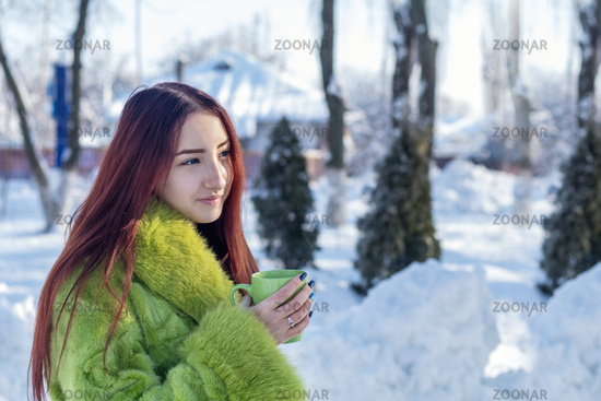 Beautiful cute pretty redhead female teenager in a green fur coat drinking coffee in the sunny winter city park.