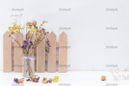 Composition of dried flowers and decoration on white cracked wall background.