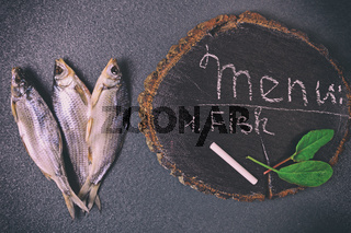 Three dried fish on a black surface