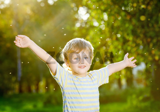 Smiling little boy with open arms in a summer garden