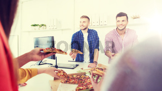 happy business team eating pizza in office