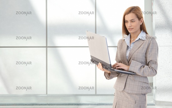 Attractive businesswoman with laptop in hands