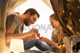 family playing tea party in kids tent at home