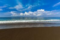 Black volcanic sand beach in Bali Island Indonesia