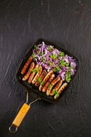 Fried sausages with onion and parsley in a pan on black background