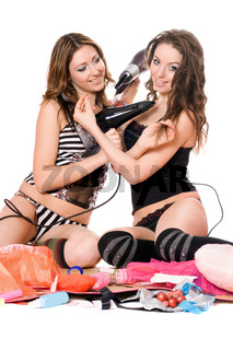 Two smiling young girlfriends with hair dryers. Isolated