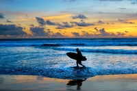 Surfer with surfboard at sunset