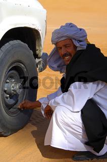 Arabischer Fahrer überprüft den Reifendruck