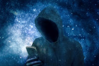 Cyber criminal in hoodie with smartphone