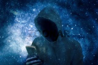 Cyberkrimineller im Hoodie mit Smartphone