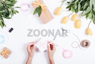 Female hands tie a pink ribbon box with gifts on a white table