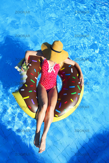 Young woman on inflatable mattress in the swimming pool