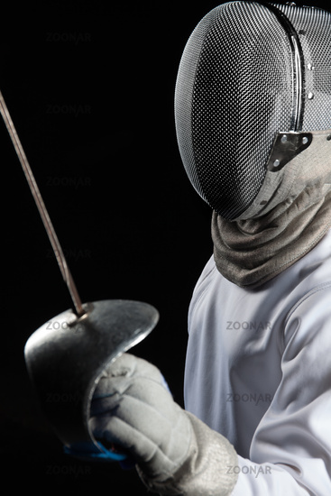 Portrait of fencer woman wearing white fencing costume practicing with the sword. Isolated on black background.