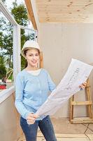 Frau als Architektin mit Bauplan