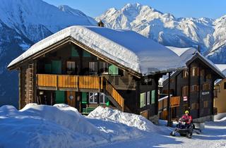 Schweizer Chalet mit einer dicken Schneedecke auf dem Dach, Bettmeralp, Wallis, Schweiz