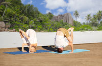 couple making yoga over tropical beach